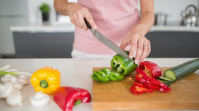 Mid section of a woman chopping vegetables in kitchen. Mid section of a young woman chopping vegetables in the kitchen at home Royalty Free Stock Photography