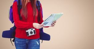 Mid section of woman with digital camera and backpack reading newspaper Royalty Free Stock Image