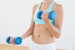 Mid section of a woman with dumbbells at fitness studio Royalty Free Stock Photo