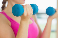 Mid section of a woman exercising with dumbbells in fitness studio Stock Photography