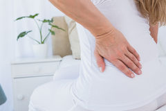 Mid section of woman getting back pain. At home in the bedroom Royalty Free Stock Photo