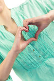Mid section of woman with heart shape of fingers Stock Photo
