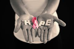 Mid section of woman holding pink ribbon with hope text Royalty Free Stock Images