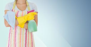 Mid section of woman holding spray bottle and napkin Royalty Free Stock Photo