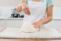 Mid section of a woman kneading dough in kitchen Stock Photo