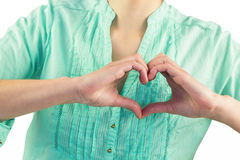 Mid section of woman making heart shape of fingers Stock Images