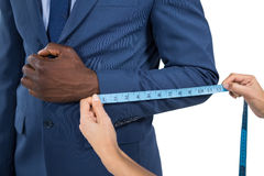 Mid section of woman measuring businessman sleeve. On white background Stock Photo