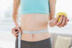 Mid section of woman measuring waist with apple in hand Stock Photography