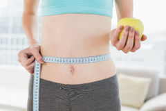 Mid section of woman measuring waist with apple in hand Stock Photo