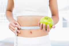 Mid section of woman measuring waist as she holds apple Royalty Free Stock Photo