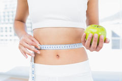 Mid section of woman measuring waist as she holds apple Royalty Free Stock Photography
