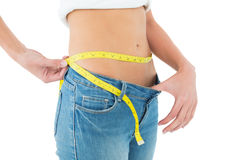 Mid section of woman measuring waist in a big sized jeans Stock Photo