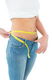 Mid section of a woman measuring waist in a big sized jeans Stock Photography