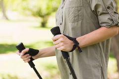 Mid section of a woman Nordic walking in park Stock Photos