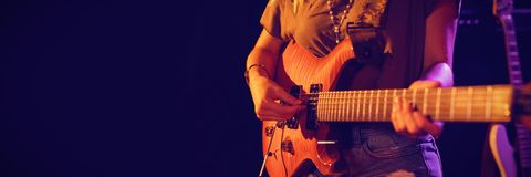 Mid section of woman playing guitar. At concert in nightclub Royalty Free Stock Photos