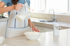 Mid section of woman pouring milk into dough at kitchen Royalty Free Stock Photo