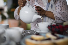 Mid section of woman pouring tea in cup Stock Photo