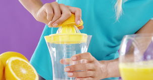 Woman preparing sweet lime juice from juicer against violet background. Mid-section of woman preparing sweet lime juice from juicer against violet background stock video footage