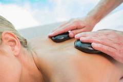 Mid section of woman receiving stone massage at health farm Stock Photos