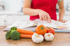 Mid section of a woman with recipe book and vegetables Royalty Free Stock Photos