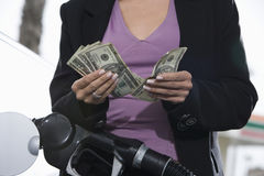 Mid Section Of A Woman Refueling Her Car While Counting Money Royalty Free Stock Image