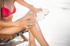Mid-section of woman sitting on armchair and applying sunscreen lotion Stock Image