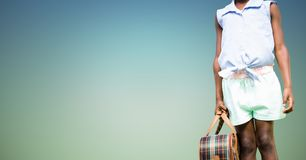 Mid section of woman standing with luggage bag. On a sunny day Stock Photo