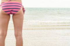 Mid section of a woman in striped bikini bottom at beach Stock Photos