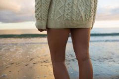 Mid section of woman in sweater standing on beach Stock Image