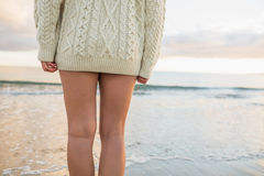 Mid section of a woman in sweater standing on beach Stock Images