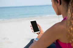 Mid section of woman using mobile phone at beach. Mid section of woman using mobile phone while sitting at beach against sky Stock Photo
