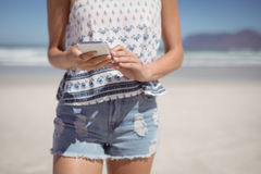 Mid section of woman using mobile phone at beach. During sunny day Royalty Free Stock Photo