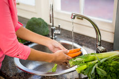 Mid section of woman washing carrots Stock Images