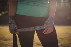 Mid section of woman wearing boxing band in hand during obstacle course royalty free stock photo