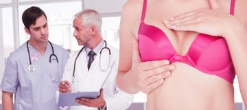 Composite image of mid section of woman in pink bra checking breast for cancer awareness. Mid section of women in pink bra checking breast for cancer awareness Stock Photos