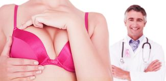 Composite image of mid section of woman in pink bra touching breast for cancer awareness. Mid section of women in pink bra touching breast for cancer awareness Stock Photography