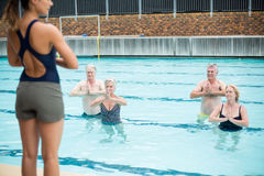 Mid section of yoga trainer assisting senior swimmers. At poolside Stock Photos