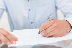 Mid section of a young man writing documents Royalty Free Stock Photos