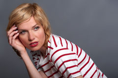 Mid shot of cute young blond fashion model crouching, in striped Stock Images