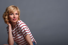 Mid shot of cute young blond fashion model crouching, in striped. Cute young blond fashion model crouching, in striped top,  isolated over grey background Stock Image