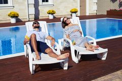 Happy couple lying on lounge chairs in front of house with pool royalty free stock images