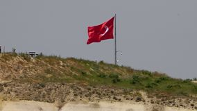 Turkish flag stands in a field. Mid shot of a Turkish flag in a hazy field blowing in the wind next to a bench stock video