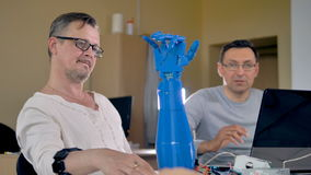 Mid shot of the two men testing bionic robotic hand. Mid shot of the two men talking and the bionic hand repeating the hand`s movements stock footage