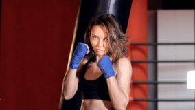 Mid shot of the woman in a boxing stance. Mid shot of the woman in a boxing stance among punching bags stock footage