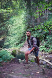 Young bearded hiker stepping rocks in mountain forest Royalty Free Stock Photo