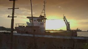 Neglected vessel at a jetty, Conakry port, Guinea. Mid still shot of empty, small, stalled, neglected, yellow painted cargo ship, afloat, docked along concrete stock video footage