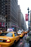 Mid-town Manhatten. Row of New York taxi cabs on busy Manhatten street Stock Photography