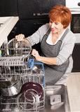 Mid Woman folding the dishes in the dishwasher Royalty Free Stock Photos