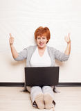 Mid woman sitting on floor with laptop Royalty Free Stock Image