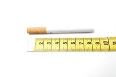 Mida la cinta y un cigarrillo Foto de archivo